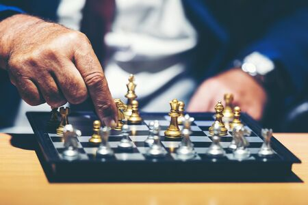 Close up hand of businessman moving chess figure in competition success play and thinking for management and planning work.  Business Concept