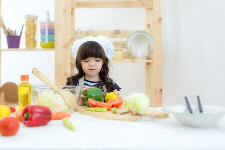 Asian beautiful kid girl cooking and cutting vegetables on kitchen, so happy and relax for leaning and education cook food.  Lifestyle Concept Banco de Imagens