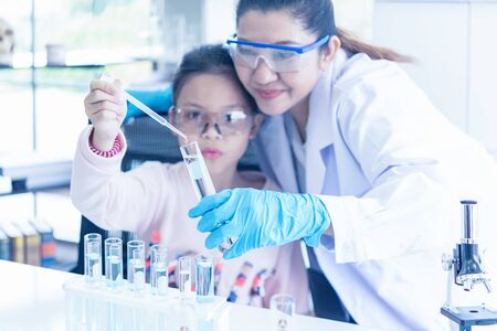 Asian children analyzing study evaluating microscope with scientist. Health care researchers doing some research with dropper chemical testing and working in life science laboratory, select focus