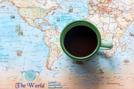 Top view of cup coffee one the word map for Traveler accessories and items man with backpack and visiting for planning travel vacations.  Travel and Summer holiday concept Banco de Imagens