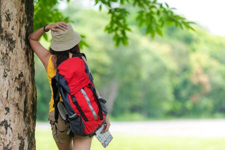 Women hiker or traveler with backpack adventure holding map to find directions and walking relax in the jungle forest outdoor for education nature on vacation. Travel and Lifestyle Concept Banco de Imagens
