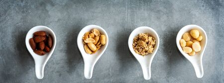 Healthy Foods. Mixed nuts in white bowls with nuts for diet on a concrete table. Different kinds of tasty and healthy nuts for text banner. Top view and copy space. Healthy Concept