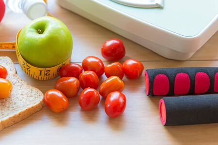 Healthy lifestyle for women diet with sport equipment, sneakers, measuring tape, fruit healthy green apples and bottle of water on wooden.  Healthy Concept.