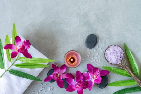 Thai Spa. Top view of hot stones setting for massage treatment and relax with purple orchid on blackboard with copy space. Green leaf with black stones pile for spa therapy. Lifestyle Healthy