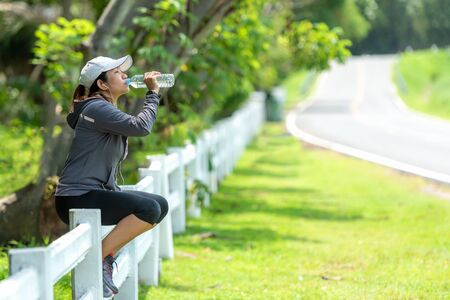 Healthy athletic asian woman is drinking pure water from the bottle refreshing herself after exercise in the nature park. Healthy and Lifestyle Concept