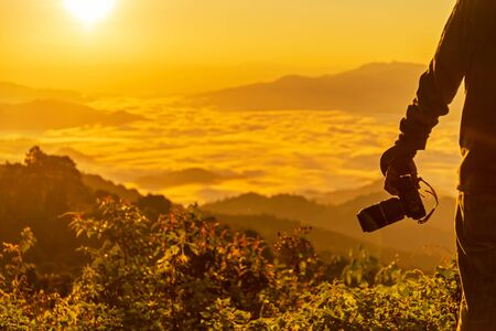 Silhouette professional man photographer holding camera for take a photo the mountain view in the sunrise.