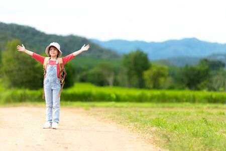 Asian girl children raise arms and standing see the outdoors, adventure and tourism for destination and leisure trips with mountain for education and relax in nature park. Travel vacations and Life Concept
