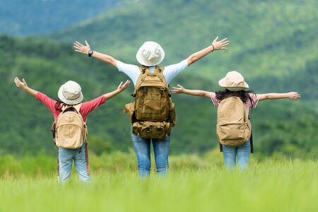 Group asian family children raise arms and standing see the outdoors, adventure and tourism for destination and leisure trips with mountain for education and relax in nature park. Travel vacations and Life Concept