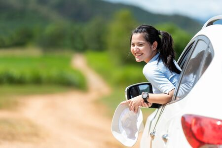Asian young woman traveler and tourism go to trips travel on  hatchback car to destination and leisure travel on the road forest in holiday vacations. Travel Concept