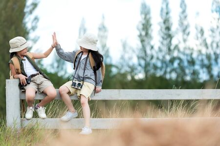 Asian two children raise give me five and sitting on the white fence outdoors, adventure and tourism for destination and leisure trips with mountain for education and relax in nature park. Travel vacations and Life Concept