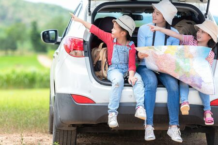 Group asian family children checking map and pointing on the car adventure and tourism for destination and leisure trips travel for education and relax in nature park .  Travel vacations 写真素材 - 128746635