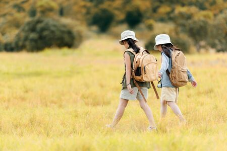 Asian two friend children holding map and walking with adventure and tourism for destination and leisure trips for education and relax in jungle and forest nature. Travel vacations and Life Concept