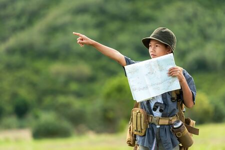 Asian boy backpack checking map and pointing in jungle forest, trips adventure and tourism for destination and leisure for education and relax in nature park.  Travel vacations Concept Banco de Imagens