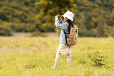 Asian girl take a photo and walking adventure, tourism for destination leisure trips for education and relax in outdoors forest nature. Travel vacations  Concept