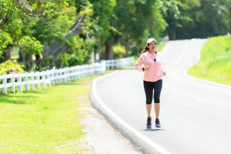 Sporty asian woman runner running and jogging through the road.  Outdoor Workout in a Park. Weight Loss and Healthy Concept