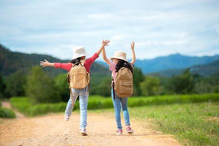 Asiatische zwei Mädchen heben die Arme und springen auf der Naturstraße, Outdoor-Abenteuer und Tourismus für Ziel- und Freizeitreisen mit Berg für Bildung und Entspannung im Dschungelpark. Reiseurlaub und Lebenskonzept