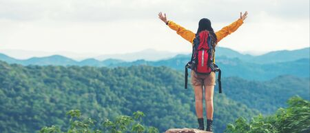 Women hiker or traveler with backpack adventure feeling victorious facing on the mountain, outdoor for education nature on vacation. Travel and Lifestyle Concept