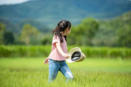 Asian girl bright running and enjoy in the field meadows outdoors, adventure and tourism for destination leisure trips for education and relax in nature park. Travel vacations and Life Concept Banco de Imagens