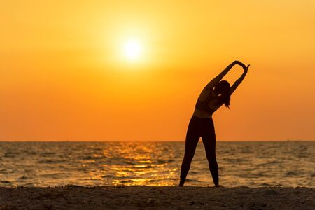 Exercise spirit lifestyle mind woman peace vitality, silhouette outdoors on the Sea sunrise, relax vital abstract. Healthy and Sport Concept Banco de Imagens