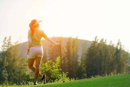 Sport Healthy. Golfer asian sporty woman relax on fairway for the put golf ball on the green golf evening time in vacations day. Healthy and Lifestyle Concept