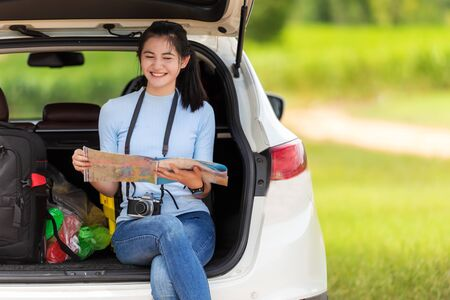 Asian smiling young woman checking map and pointing on the car adventure and tourism for destination leisure trips travel education and happy relax in nature park. Travel vacations Banco de Imagens