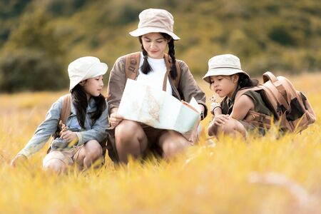 Group asian family children checking map in the jungle adventure and tourism for destination leisure trips for education and relax in nature park.  Travel vacations and Life Concept Banco de Imagens