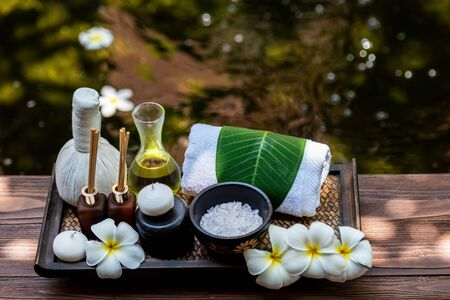 Thai spa composition treatments aroma therapy with candles and Plumeria flowers on wooden table close up. Healthy and Relax Concept 版權商用圖片