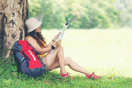 Tourism asian lifestyle women and traveler with backpack adventure holding map to find directions in the jungle forest destination and leisure outdoor for education nature. Travel and Trips Concept