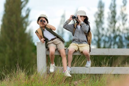 Asian two friend children take a photo and see binoculars for adventure and tourism for destination and leisure trips for education relax in jungle forest nature. Travel vacations Concept