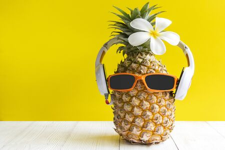 Summer in the party.  Hipster Pineapple Fashion in sunglass and music bright beautiful color in holiday, Creative art fruit for tropical style on the beach vibes, yellow background.  Fashion Summer Vacation Concept Banco de Imagens