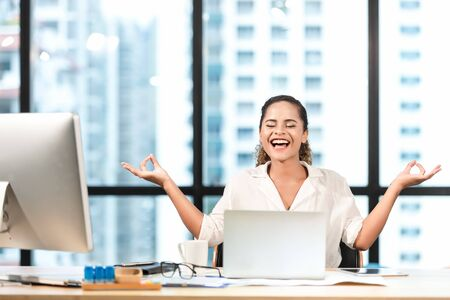 Relax time.  Successful smiling business woman relaxing and  meditating after working in modern office, mindful peaceful and practicing breathing yoga exercises and resting healthy care.  Business Concept