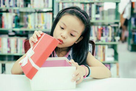 Confezione regalo per bambina. Scatola bianca con fiocco rosso nelle mani sorridenti di una ragazza asiatica per fare un regalo in biblioteca, un regalo felice e a sorpresa nella scatola. Concetto di anniversario e celebrazione