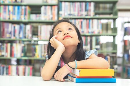 Kids asian beautiful girl reading books and thinking for education and go to school in library. Education and Lifestyle Concept