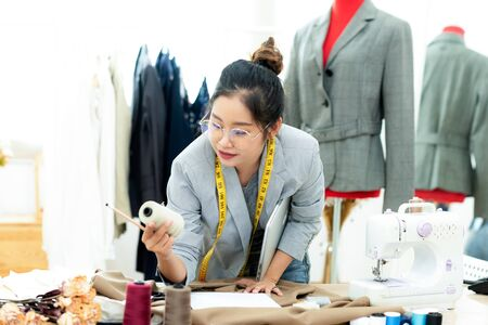 Asian young women fashion designer  working on her designer in the showroom,  Lifestyle Stylish tailor taking measurements on mannequin in studio.  Business and Industry small Concept Banco de Imagens