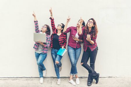 Asian group lifestyle woman standing and holding notebook, smartphone and book for education outdoors,  adult of people pointing up on free space over white brick wall.  Education Concept