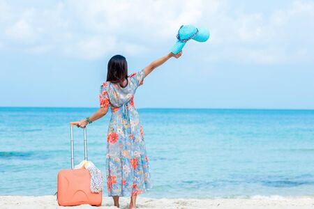 Travel Plan. women traveler holding orange luggage walking on the beach. Traveler and Tourism planning trips summer vacations with Travelers accessories summertime. Summer Concept