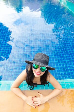 Summer time and Vacations. Women lifestyle relaxing and happy in luxury swimming pool sunbath, summer day at the beach resort in the hotel. Summer Concept Banco de Imagens