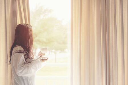 Asian woman in bedroom drinking coffee after wake up and relax mood in holiday near window, sunny morning. Lifestyle Concept.