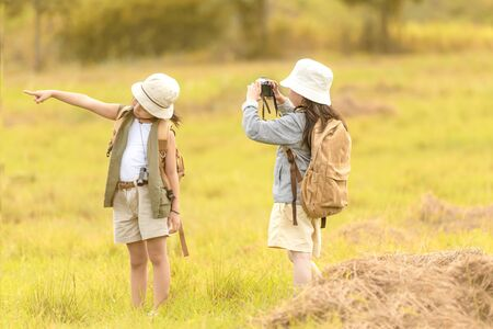 Asian two friend children take a photo and walking with adventure and tourism for destination and leisure trips for education and relax in jungle and forest nature. Travel vacations and Life Concept Banco de Imagens