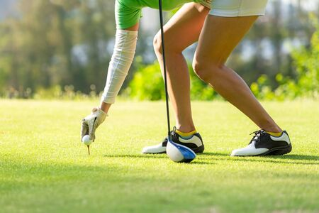 Hand asian sporty woman putting golf ball on tee with club in golf course on evening on time for healthy sport. Lifestyle and Sport Concept