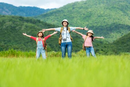 Group asian family children raise arms and standing see mountain outdoors, adventure and tourism for destination leisure trips for education and relax in nature park. Travel vacations and Life Concept Stockfoto