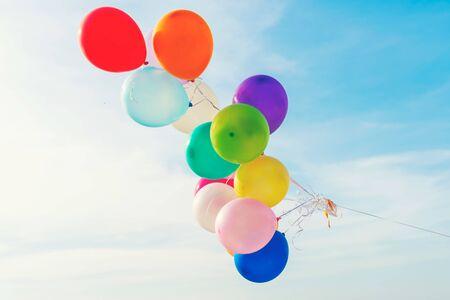 일몰 열대 해변 화창한 날 휴식을 위한 캔버스 침대가 있는 다양한 색상의 풍선. 여름 개념입니다.