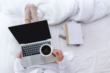 Close up legs women on white bed in the bedroom. Women working on laptop and drinking coffee in morning relax mood in winter season. Lifestyle Concept.