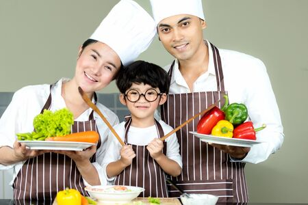 Healthy Family. Father and Mother with son cooking salad fresh vegetables for diet in kitchen.  Smiling kid boy help family making cookie, so happy and enjoy in holiday.  Family Concept. 写真素材