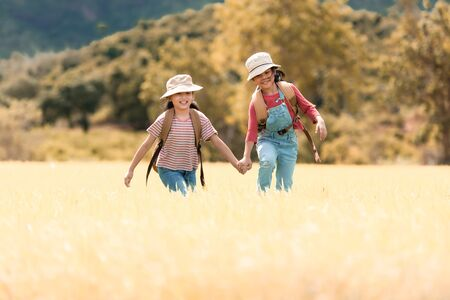 Asian girl and friend running and enjoy in the field meadows outdoors, adventure and tourism for destination leisure trips for education and relax in nature park. Travel vacations and Life Concept