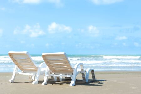 Summer Travel. White chair on sandy beach against blue sea and sky background, copy space. Summer vacation concept. 写真素材