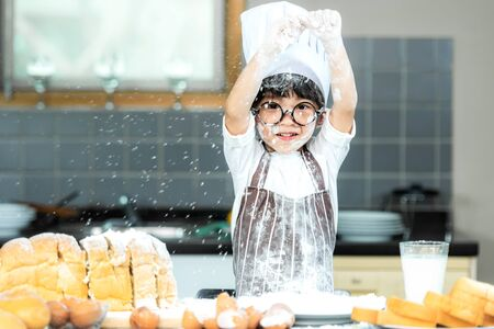 Healthy Family.  Smiling asian boy cooking toast and make bread in holiday.  Kid making and leaning sweet food, so happy and enjoy.  Family and Healthy Concept. 写真素材