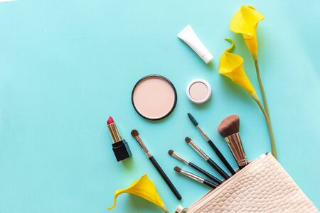 Makeup cosmetics tools and beauty cosmetics gift, products and facial cosmetics package lipstick with yellow lily flower on blue background, top view and copy space.  Lifestyle Beauty Concept 写真素材