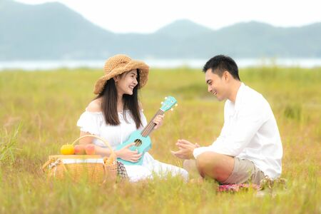 Lifestyle couple picnic sunny time. Asian young couple having fun and relax playing guitar on picnic in the meadow and field in holiday.  Romantic and In love.   Lifestyle concept