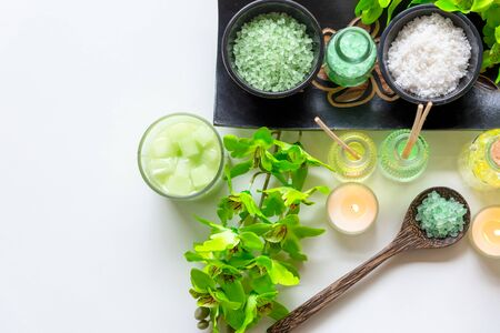 Thai Spa Treatments aroma therapy salt and nature green sugar scrub and rock massage with green orchid flower on wooden white with candle. Thailand. Healthy Concept.